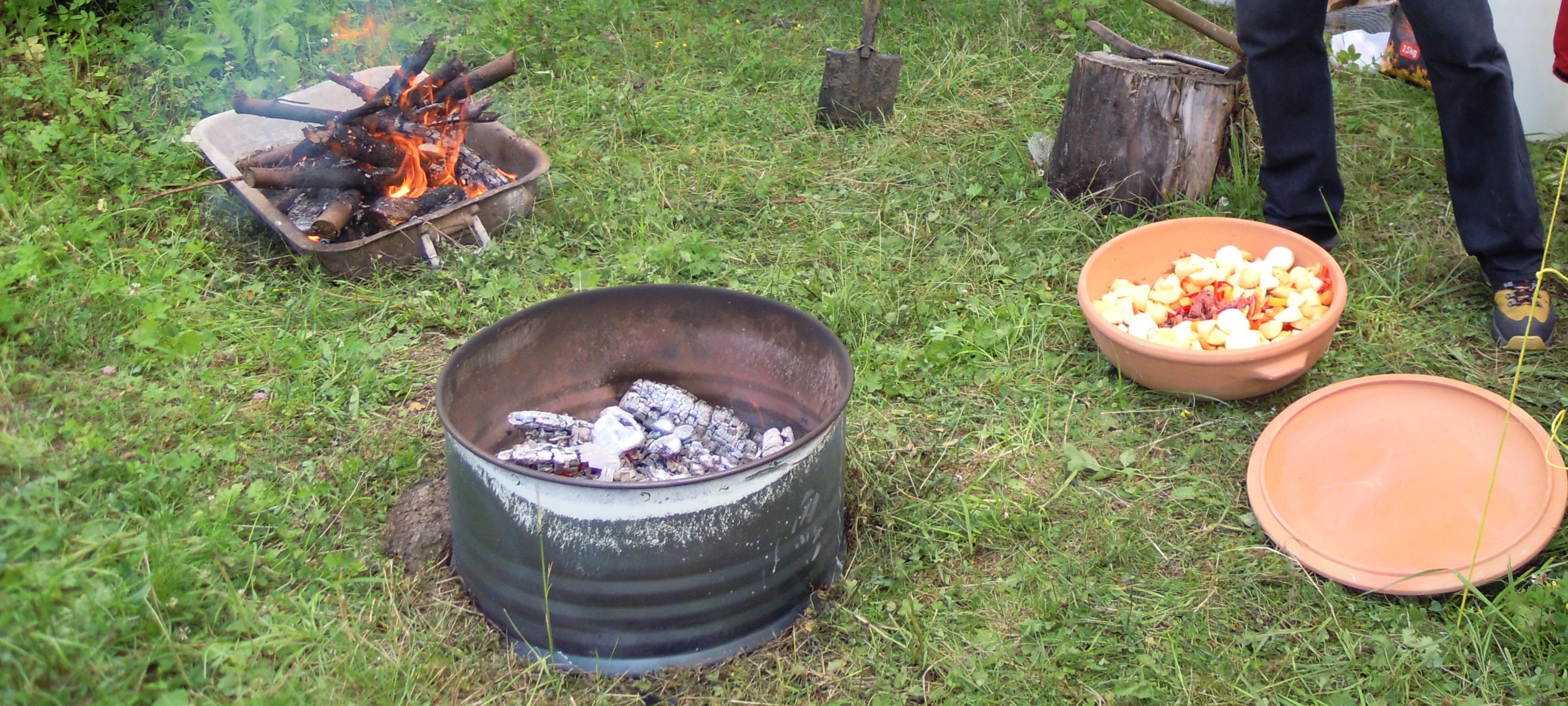 Příprava skruže se žhavým uhlím. do které se vloží hliněný hrnec a zasype se další vrstvou žhavého uhlí
