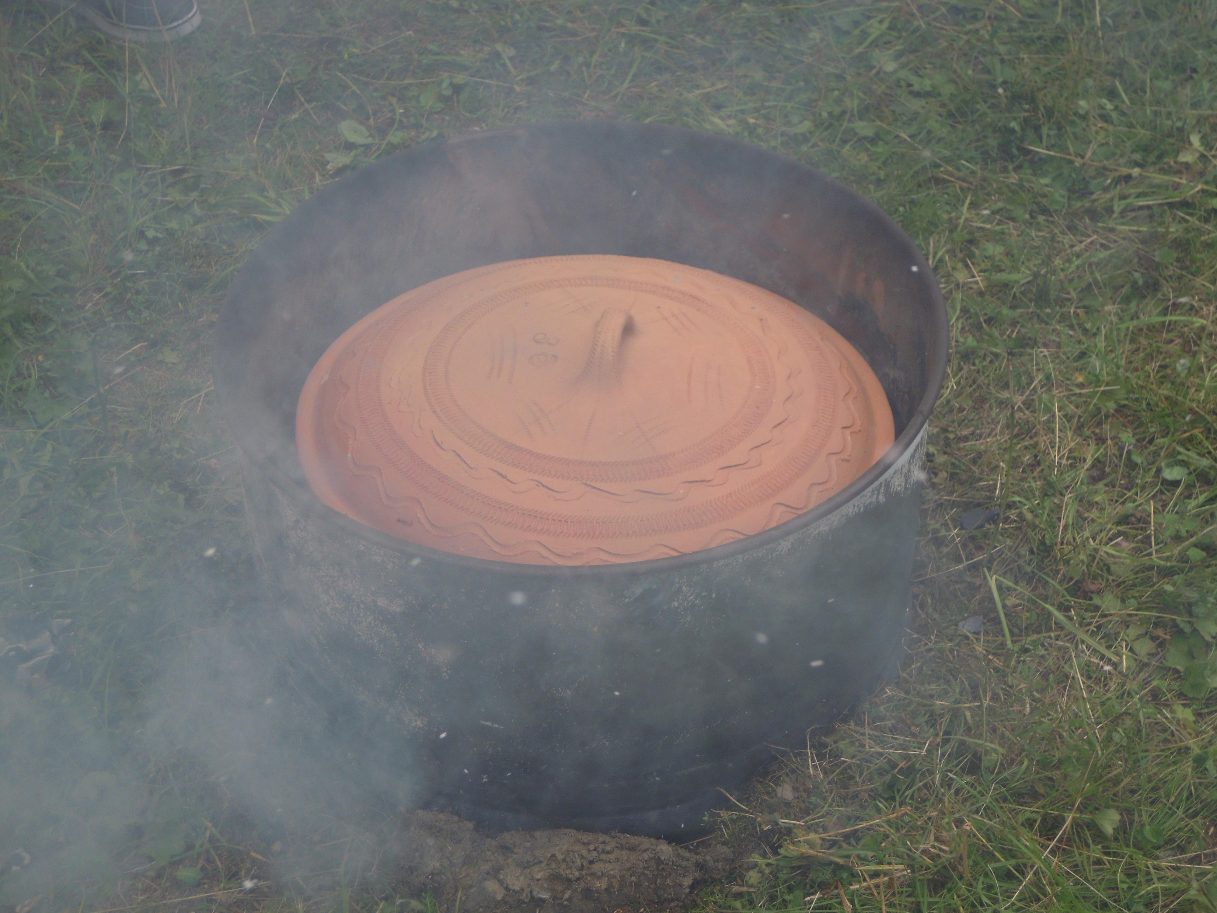 Vložení hliněného hrnce do skruže se žhavým uhlím